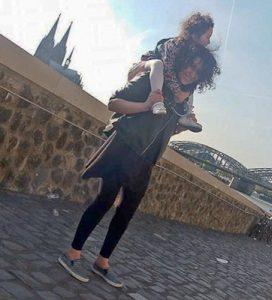 Jackleen mit ihrer Tochter auf den Schultern und den Kölner Dom im Hintergrund